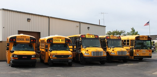 Five buses in the ServiCar bus fleet, holding a variety of passengers with adaptive equipment for special needs transporation.